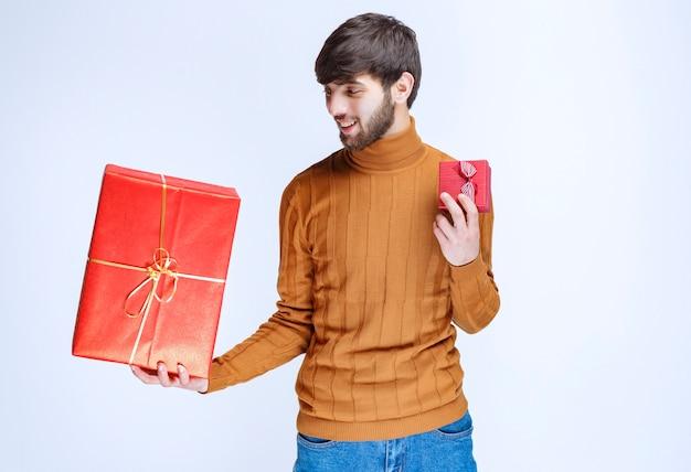 Человек, держащий большие и маленькие красные подарочные коробки в обеих руках.