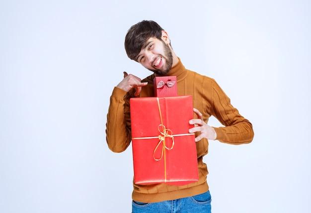 Uomo che tiene scatole regalo rosse grandi e piccole e chiede una chiamata.