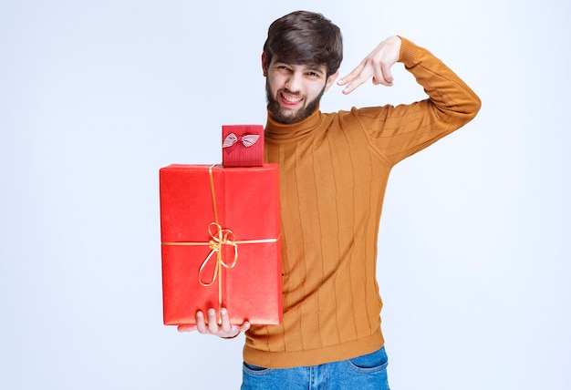 Man holding big and small red gift boxes and demonstrating them.