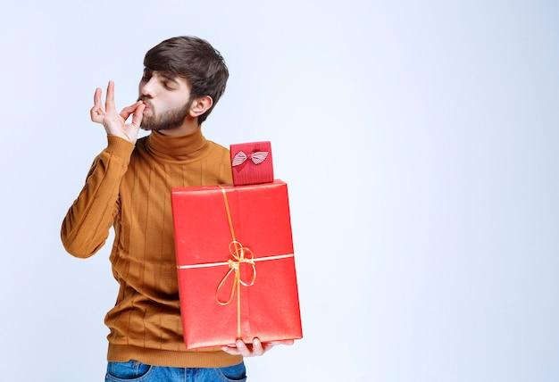 Uomo che tiene scatole regalo rosse grandi e piccole e si diverte.