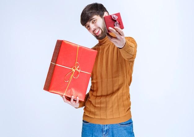 Uomo che tiene in mano scatole regalo rosse grandi e piccole e ne offre una alla sua ragazza.