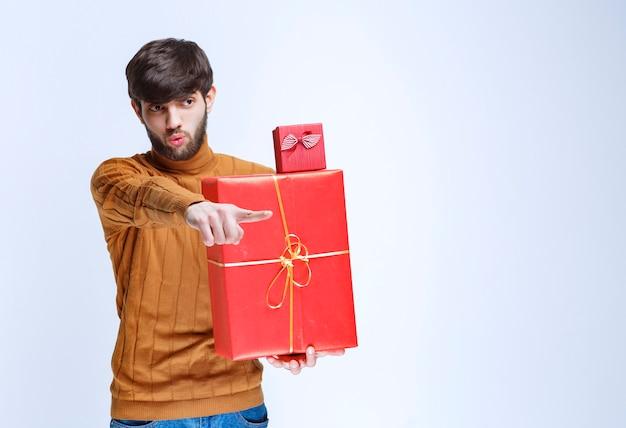 Uomo che tiene scatole regalo rosse grandi e piccole e che punta a qualcuno.