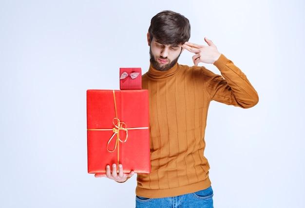Uomo che tiene scatole regalo rosse grandi e piccole e pensa.