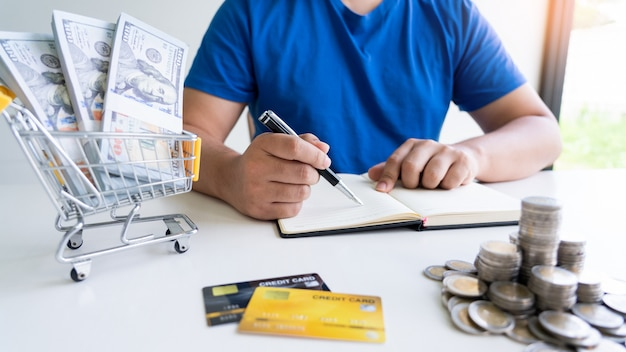 Man holding bills and counting money with pen of household daily expenses
