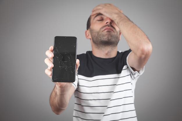 Man holding black broken smartphone. broken screen