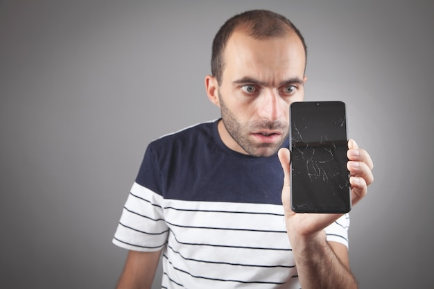黒の壊れたスマートフォンを持っている男。壊れた画面