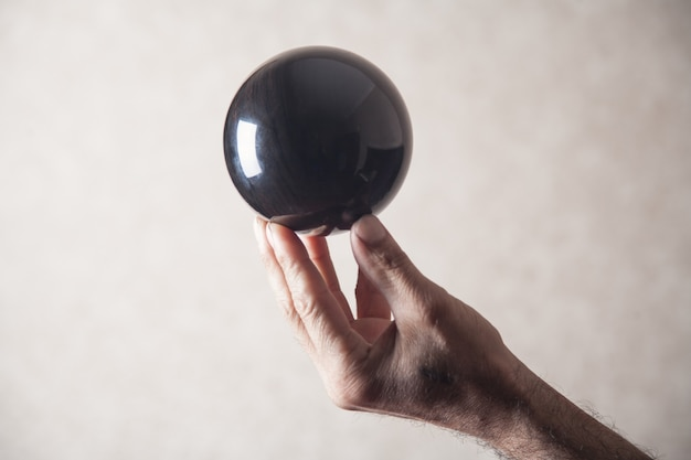 Мужчина держит черный хрустальный шар.