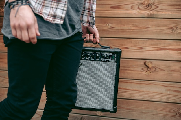 Man holding black electric guitar amplifier for musicians