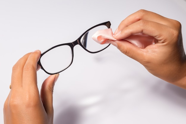 Man holding the black eye glasses spectacles with shiny black frame isolated on white