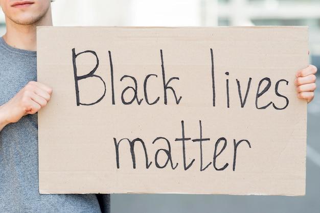 Man holding black lives matter quote on cardboard