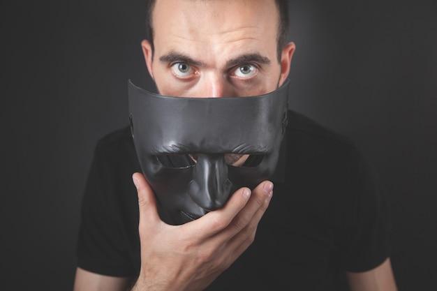 검은 마스크를 들고 남자입니다. 가짜, 익명
