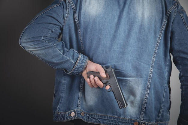 A man holding a black pistol in his hand threatening