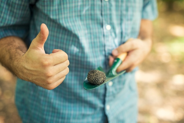 Man holding black truffle with thumb up in nature
