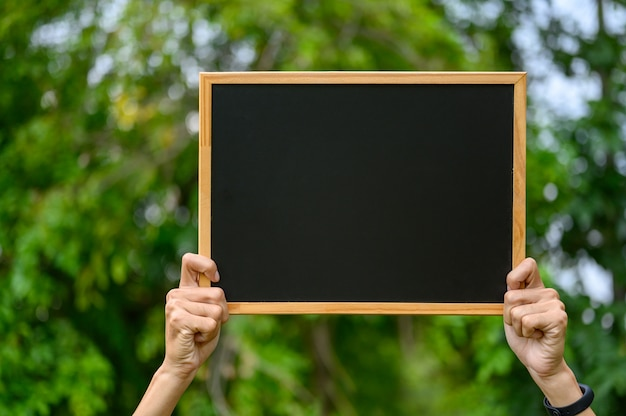 The man holding a blackboard at the outdoor field