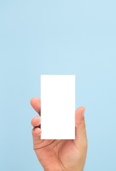 Man holding blank business card on light blue background