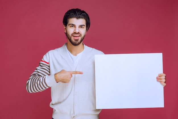 Man holding a blank idea board and pointing at it for attention.