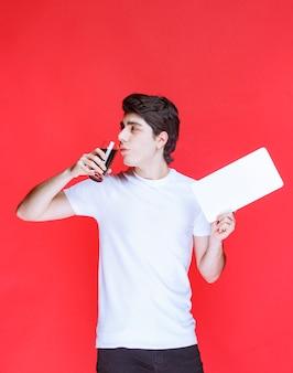 Uomo che tiene una carta bianca e beve un bicchiere di succo.