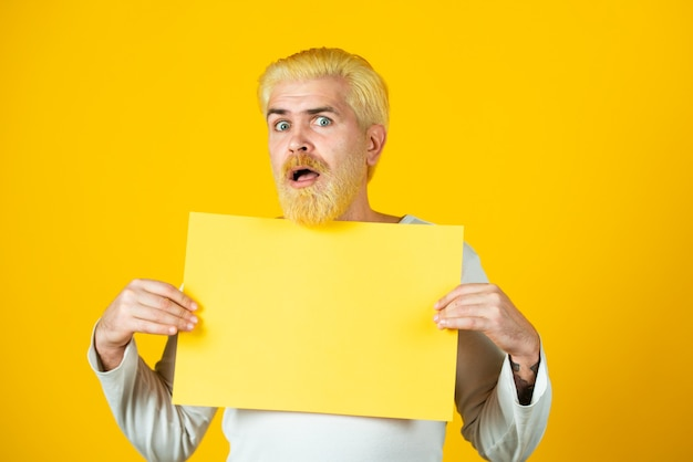 Man holding a blank sheet of paper isolated on yellow background