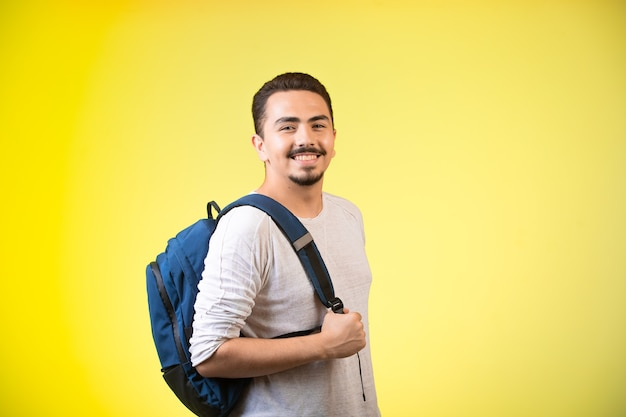Man holding a blue backpack and looks happy.