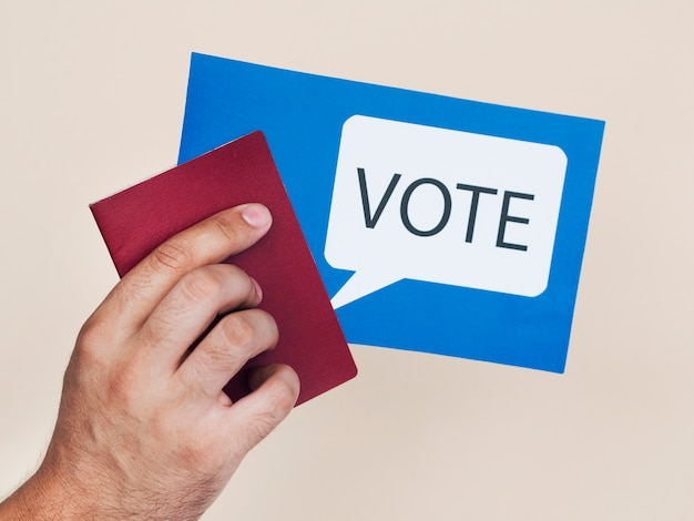 Man holding a blue card with voting speech bubble