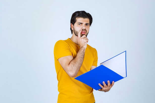 Man holding a blue folder and thinking.
