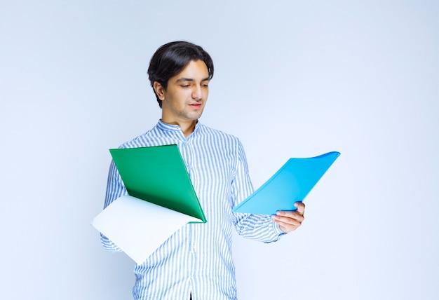 Uomo che tiene le cartelle di report blu e verdi e le controlla. foto di alta qualità