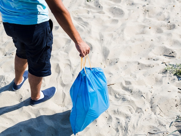 Man holding blue plastic bag of garbage at beach