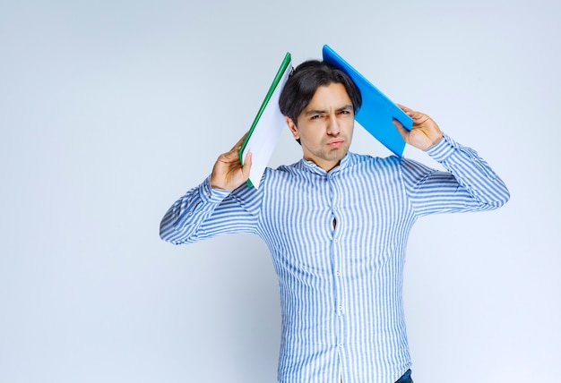 Man holding blue reporting folders over his head. high quality photo