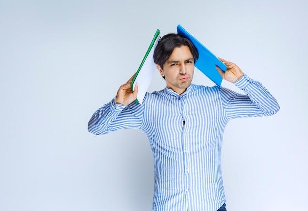 그의 머리 위에 파란색보고 폴더를 들고 남자입니다. 고품질 사진