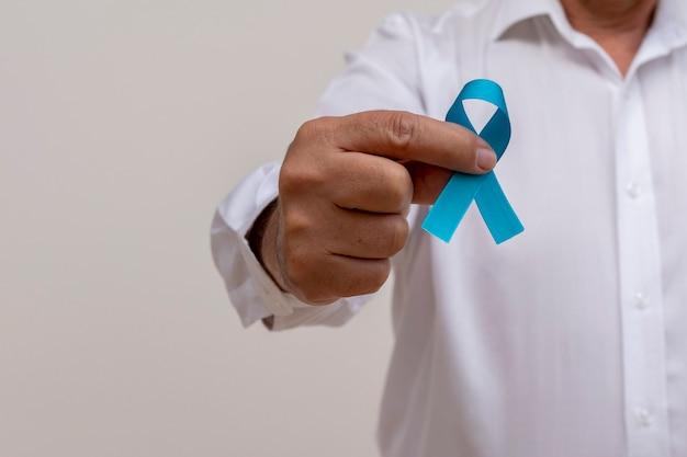 青いリボンを持っている男。青い11月。前立腺がん予防月間。男性の健康。
