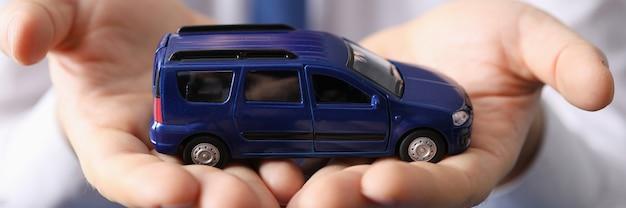 그의 손 근접 촬영에 파란색 장난감 자동차를 들고 남자