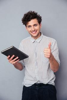 Мужчина держит книгу и показывает палец вверх