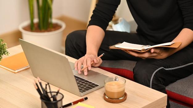 Мужчина держит книгу и работает с ноутбуком в гостиной.