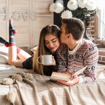 Man holding book in hand kissing her girlfriend holding cup of coffee lying on bed