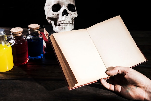 Man holding books on background with halloween decorations