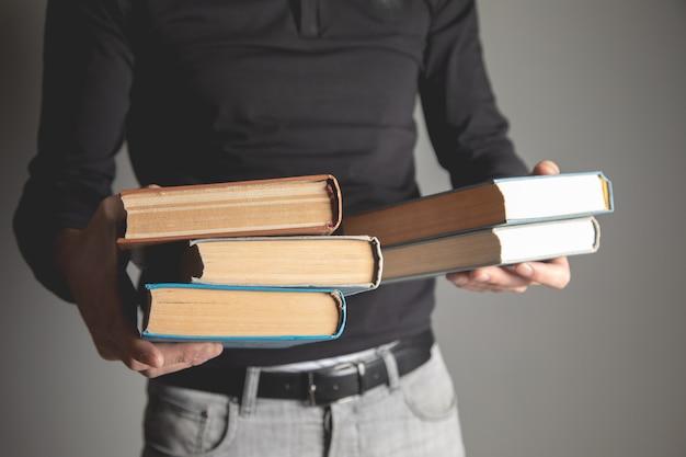 灰色の背景に彼の手で本を持っている男
