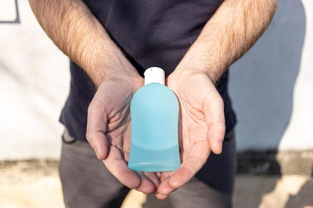 Man holding bottle of antibacterial sanitizer
