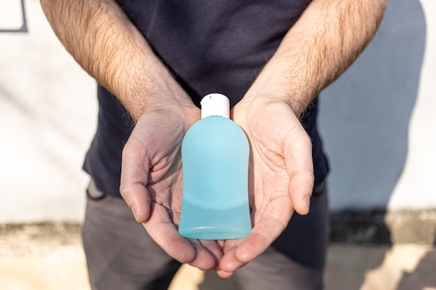 Мужчина держит бутылку антибактериального дезинфицирующего средства