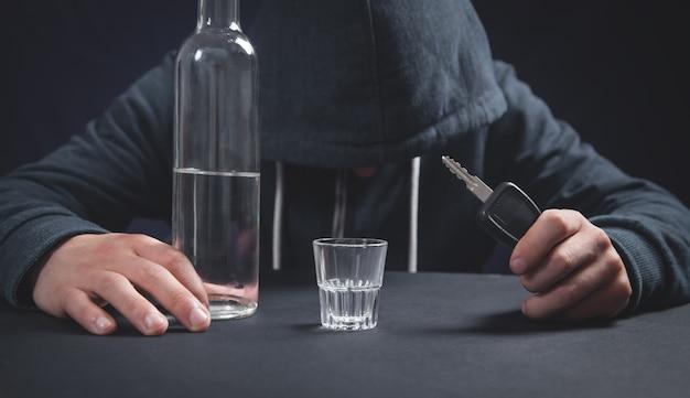 ウォッカと車の鍵のボトルを保持している男。飲酒運転