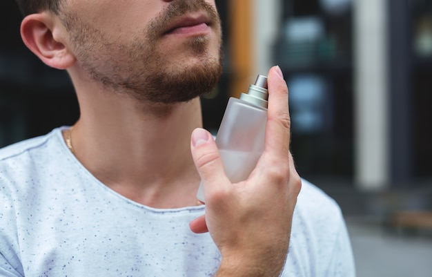 Man holding bottle of perfume