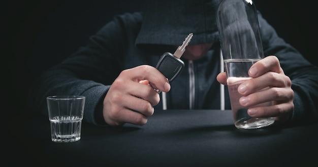 Man holding bottle of vodka and car key.