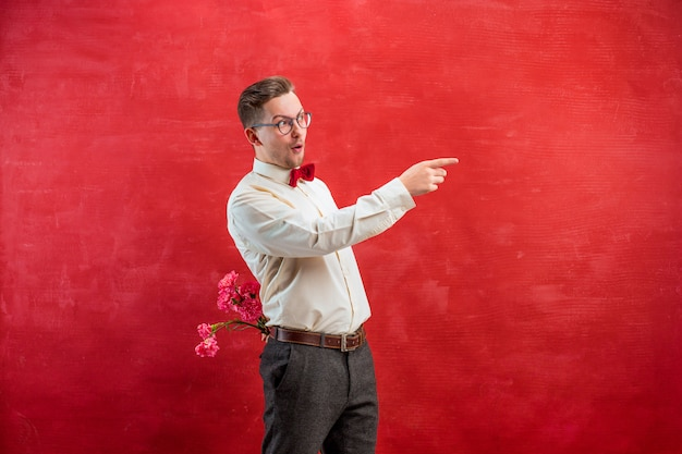 Man holding bouquet of carnations behind back