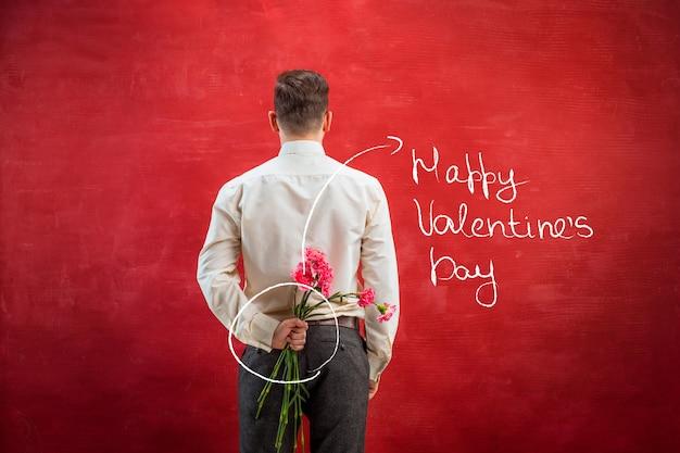 赤いスタジオの背景に後ろにカーネーションの花束を持っている男。幸せなバレンタインデーのコンセプト