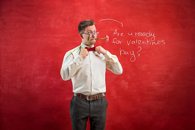 赤いスタジオの背景にカーネーションの花束を保持している男。幸せなバレンタインデーのコンセプト