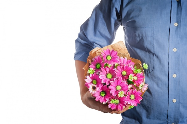 Man holding a bouquet of pink flowers wearing a blue shirt