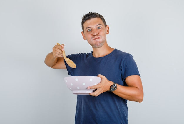 Man holding bowl and spoon with blowing cheeks in blue t-shirt and looking hungry. front view.