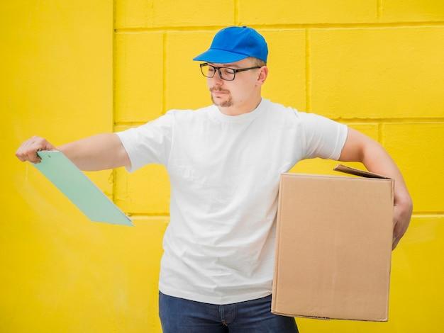 Мужчина держит коробку и буфер обмена
