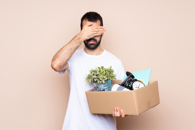 Man holding a box and moving in new home covering eyes by hands. do not want to see something