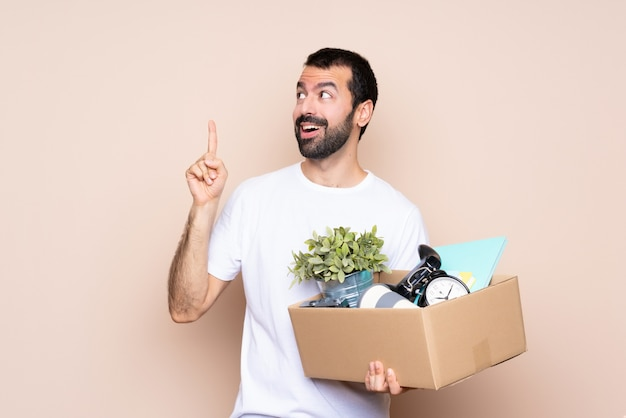 Man holding a box and moving in new home over isolated wall intending to realizes the solution while lifting a finger up