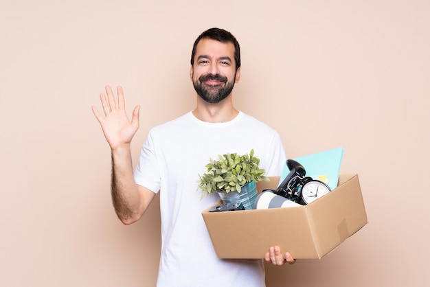 Man holding a box and moving in new home saluting with hand with happy expression